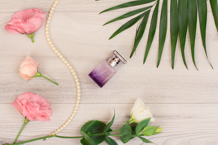Bottle of perfume, beads on a string with white and pink flowers and green leaves on wooden background. Woomen cosmetics. Top view. 스톡 콘텐츠