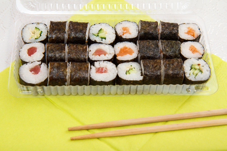 Sushi rolls in nori seaweed sheets with avocado and red fish in plastic box with wooden sticks on napkin. Delivery of packaged food.