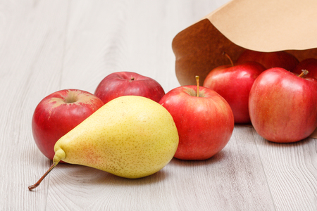 Ripe yellow pear and red apples with paper bag on wooden desk. Healthy organic food.