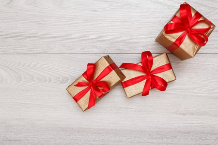 Three gift boxes tied with red ribbons on gray wooden Stock Photo
