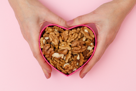Woman holding a box in heart shape with peeled walnuts on pink