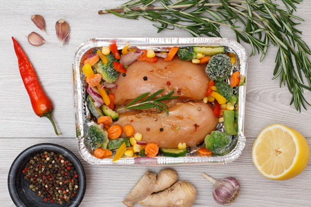 Couple of raw chicken breasts or fillet with frozen vegetables in metal container