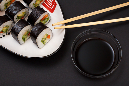 Sushi rolls in nori seaweed sheets with avocado and red fish on ceramic plate. Imagens