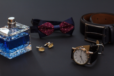 Cologne for men, cufflinks, bow tie, watch with a black leather strap and leather belt with metal buckle on black