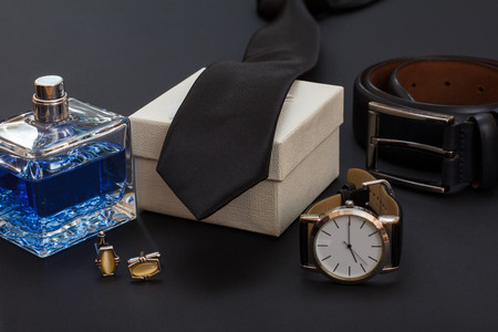 Cologne for men, cufflinks, white gift box, tie, watch with a black leather strap and leather belt with metal buckle on black 免版税图像