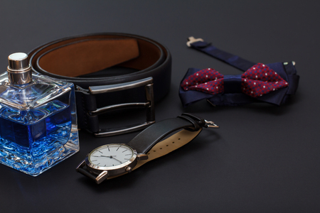 Cologne for men, leather belt with metal buckle, watch with a black leather strap and bow tie on black Reklamní fotografie