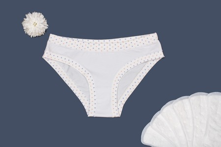 Beautiful white panties with sanitary napkins on gray background. Women underwear set. Top view.