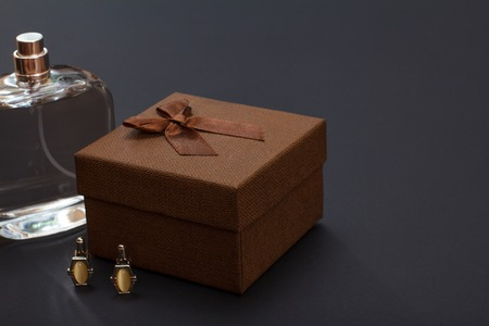 Cologne for men, brown gift box and cufflinks on black background. Accessories for men.