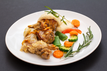 Rabbit legs baked in white wine with bechamel sauce on a white ceramic plate with vegetables and rosemary on black background. Dietary rabbit meat cooked in oven.