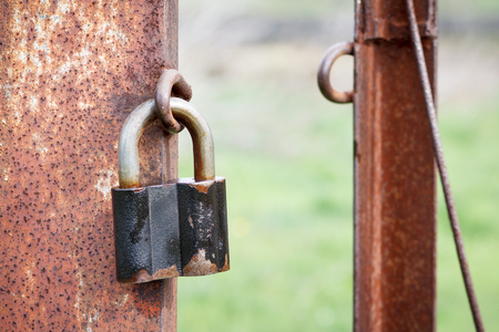 The old padlock hangs on a column of an iron rusty fencing with green yard on the background.