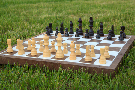 Chess board with chess pieces on green grass in daylight. Selective focus on white pieces. Outdoors chess game. 免版税图像