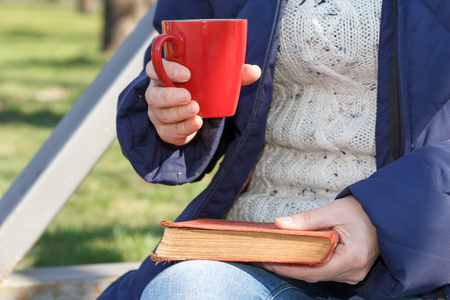 Woman holding red cup of coffee and old book, sitting on a bench in the city park. 版權商用圖片