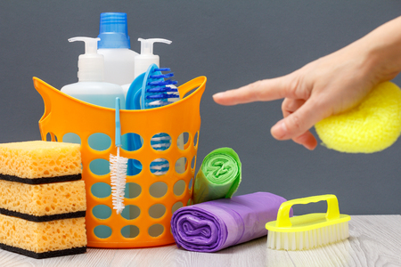 Plastic basket with bottles of dishwashing liquid, detergent for microwave ovens and stoves with female hand. Brush, garbage bags and sponges on gray background. Washing and cleaning concept.