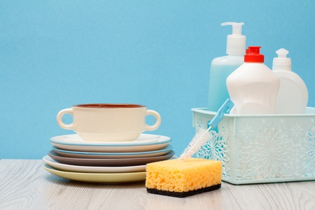 Plastic bottles of dishwashing liquid, glass and tile cleaner in basket, brush, sponge, clean plates and bowl on blue background. Washing and cleaning concept.