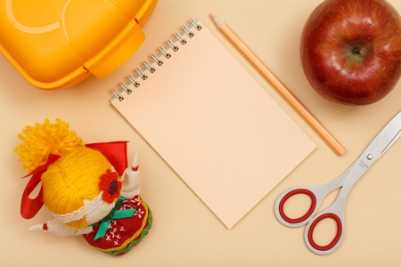 School supplies. Notebook, pencil,scissors, lunch box, apple and doll on beige background. Top view with copy space. Back to school concept. Pastel colors.