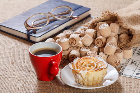 Wooden lotto barrels in sac and game cards for a game in lotto with notebook, glasses, red cup of coffee and homemade biscuit in the form of rose on white saucer.
