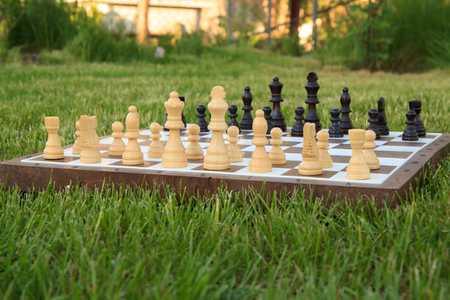 Chess board with chess pieces on green grass in daylight. Selective focus on white pieces. Outdoors chess game. Stock fotó