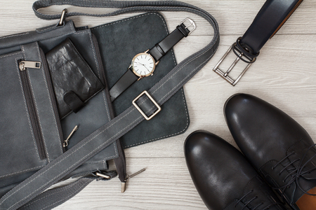 Leather shoulder bag for men with wallet and wristwatch on it, belt for men and pairs of black leather mens shoes with gray wooden Reklamní fotografie