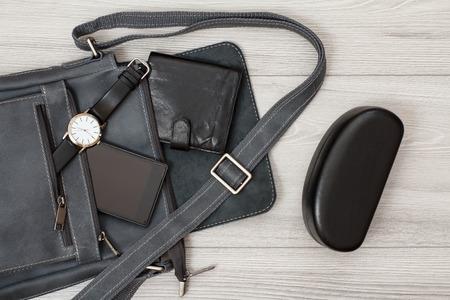 Leder Umhängetasche für Herren mit Handy, Uhr und Geldbörse drauf, Brillenetui auf grauem Holz