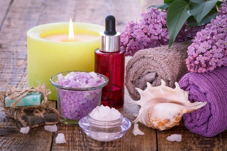 Soap, red bottle with aromatic oil, burning candle, bowls with sea salt, sea shell, lilac flowers and towels for bathroom procedures on wooden boards. 写真素材