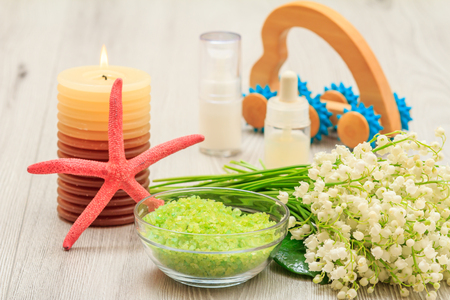 Bottles with cream for face skin and aromatic oil, bowl with sea salt, burning candle, starfish, hand massage and bouquet of lilies of the valley on wooden