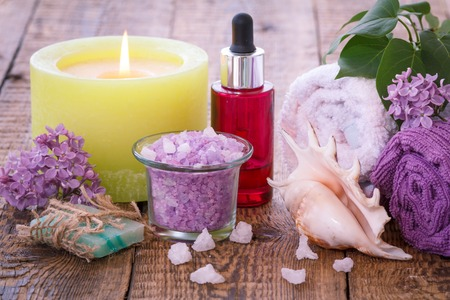 Soap, red bottle with aromatic oil, burning candle, bowl with sea salt, sea shell, lilac flowers and towels for bathroom procedures on wooden boards.