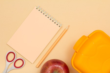 School supplies. Notebook, color pencil, apple, scissors and lunch box on beige