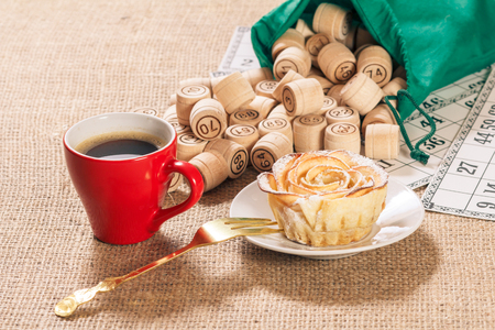 Wooden lotto barrels in green pouch and game cards for a game in lotto with cup of coffee and homemade biscuit in the form of rose on white saucer.