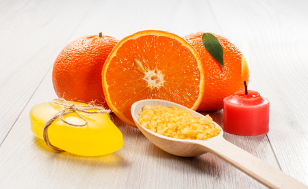 Cut orange with two whole oranges, yellow soap, wooden spoon with sea salt and burning red candle on wooden desk.