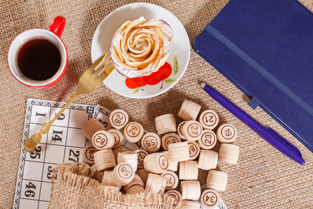 Wooden lotto barrels in pouch and game cards for a game in lotto with notebook, pen, cup of coffee, fork and homemade biscuit in the form of rose on white saucer. Top view.