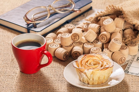 Wooden lotto barrels in pouch and game cards for a game in lotto with notebook, glasses, cup of coffee and homemade biscuit in the form of rose on white saucer.