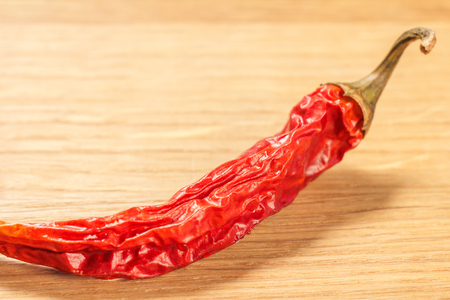 Close up cut dried red pepper on wooden cutting board. Shallow depth of field.