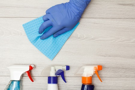 Hand in rubber glove holding blue napkin with bottles of detergent on wooden boards. Cleaning tools and equipment. Top view Stockfoto