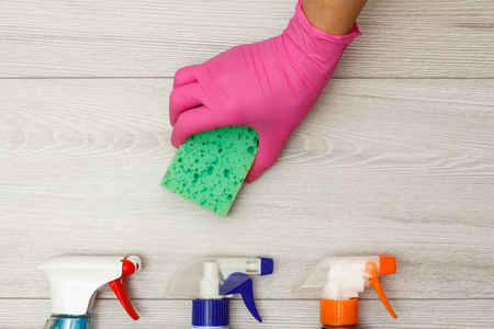 Hand in pink rubber glove holding sponge with bottles of detergent on wooden boards. Cleaning tools and equipment. Top view