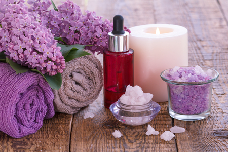 Bowls with sea salt, burning candle, red bottle with aromatic oil, lilac flowers and towels for bathroom procedures on wooden boards.