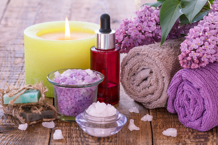Handmade soap, burning candle, bowls with sea salt, red bottle with aromatic oil, lilac flowers and towels for bathroom procedures on wooden boards. Spa products and accessories.