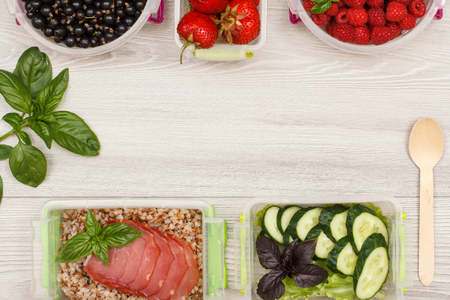 Plastic meal prep containers with boiled buckwheat porridge and slices of meat, fresh cucumbers and salad, currant, strawberries, raspberries and wooden spoon on gray background. Top view. Stock Photo