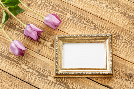 Vintage photo frame with lilac tulips and copy space on old wooden boards. Top view with copy space. Standard-Bild