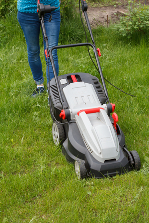 Woman is operating with lawn mower in the garden. Mower grass equipment. Mowing gardener care work tool.