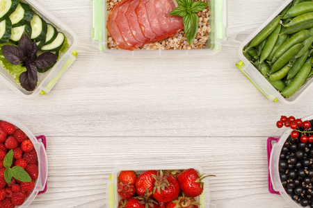 Plastic meal prep containers with black currant, strawberries, raspberries, green peas, boiled buckwheat porridge and slices of meat, fresh cucumbers and salad on grey background with copy space Stock Photo