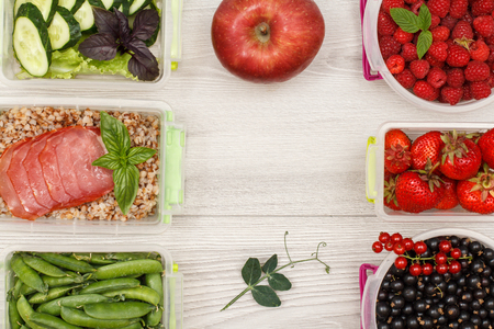 Apple and plastic meal prep containers with fresh strawberries, raspberries, boiled buckwheat porridge and slices of meat, cucumbers and salad, green peas, wooden spoon on gray background. Top view Stock Photo