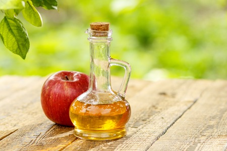 Apple vinegar in glass bottle with cork and fresh red apple on old wooden boards with blurred green natural background. Organic food for health