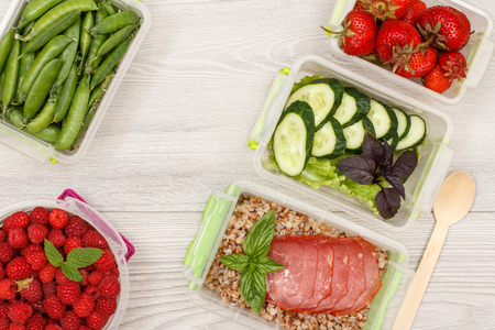 Plastic meal prep containers with fresh strawberries, raspberries, boiled buckwheat porridge and slices of meat, cucumbers and salad, green peas, wooden spoon on gray background. Top view.