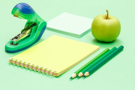 Color pencils, apple, notebook, note paper and stapler on green