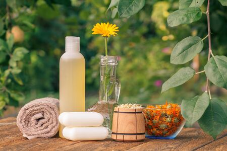Spa products and accessories. Towel, soap and plastic bottle with marigold extract, calendula flowers in a glass flask and wooden bowl with dry flowers of chamomile on wooden boards.
