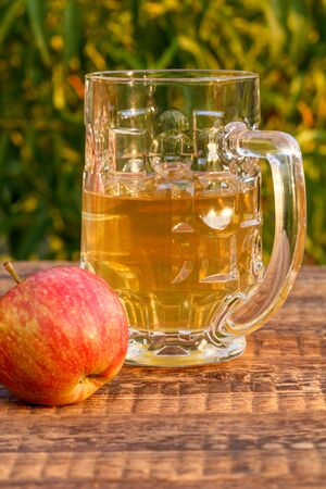 Glass goblet of apple cider and harvested apples on wooden boards with leaves of a tree