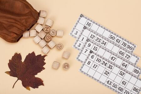 Wooden lotto barrels with open bag, dry autumn leaf and game cards on beige background. Board game lotto. Top view. Standard-Bild