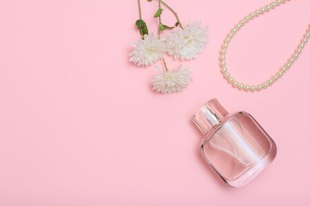 Bottle of perfume, beads and white flowers on a pink background. Women cosmetics and accessories. Top view.