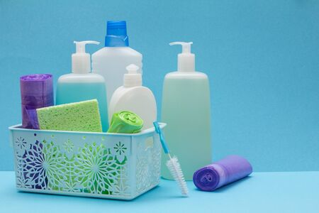 Plastic bottles of dishwashing liquid, glass and tile cleaner in basket, sponges, garbage bags and brushes on blue background. Washing and cleaning concept.