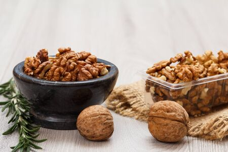 Peeled and unpeeled walnuts in stone bowl and plastic container with sackcloth and rosemary on a gray wooden Imagens